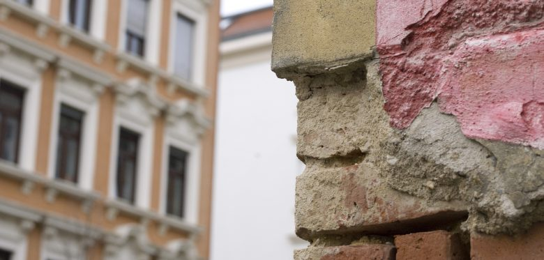Zwei Häuserfronten sind zu sehen, die im Vordergrund ist alt und morsch, die im Hintergrund auch schon historisch.