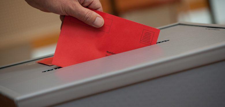 Eine Wahlurne, in der der Stimmzettel eingeworfen wird. Die Wahlurne ist grau, der Stimmwahlumschlag ist rot.