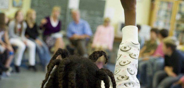 Das Bild zeigt eine Schulklasse und einen Stuhlkreis mit Schülern. Ein Mädchen mit Rastalocken hebt die Hand und meldet sich zu Wort.