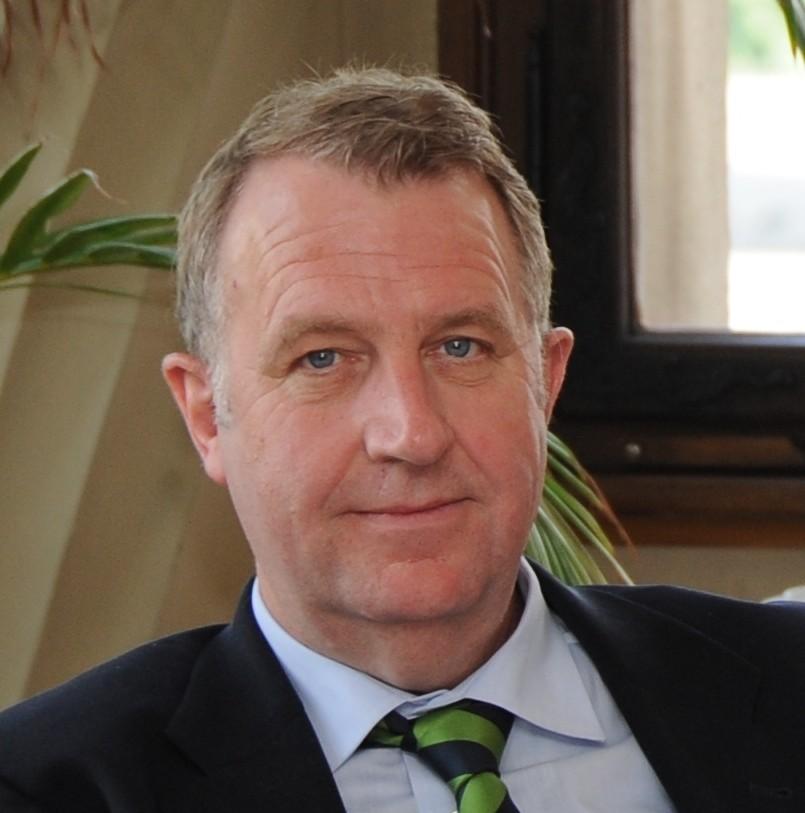 Man sieht ein Portrait-Foto von Karl Janssen in dunklem Anzug mit grüner Krawatte.