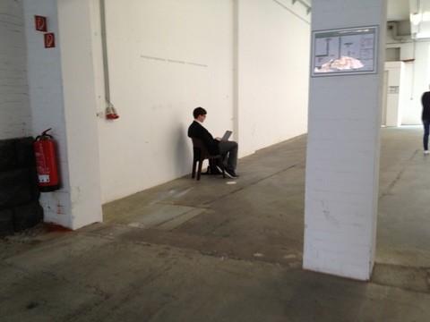 Das Bild zeigt eine leere Werkhalle mit weißen Wänden, hier sitzt einsam ein Mensch mit einem Laptop auf den Knien auf einem Hocker sitzend, mit dem Rücken zum Fotografen.