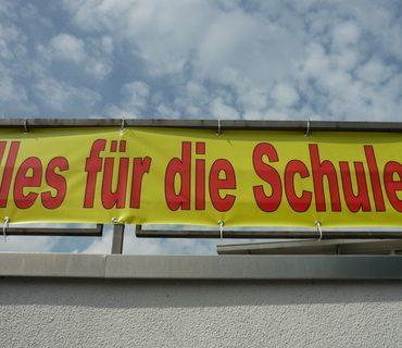 """Das Bild zeigt ein Werbebanner mit der Aufschrift """"Alles für die Schule"""" in den Farben rot und gelb vor einem blauen Himmel mit ein paar weißen Wölkchen."""