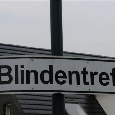 """Das Bild zeigt ein Verkehrsschild mit der Aufschrift """"Blindentreff"""", es hängt an einem Verkehrsmast gut sichtbar, im Hintergrund ist ein Häuserdach zu erkennen sowie grauer Himmel darüber."""