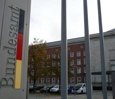 Das Bild zeigt die Hausfront des Bundesamtes für Migration und Flüchtlinge in Nürnberg, mit einem Zaun davor und den Nationalfarben von Deutschland, schwarz, rot, gelb.
