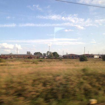 Das Bild zeigt grünes Wiesenland und darüber blauen Himmel, im Hintergrund kann man eine Siedlung erahnen. Aufgenommen ist es aus einem fahrenden Zug.