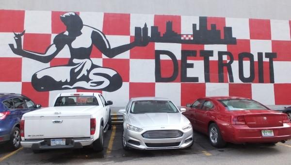 drei Autos vor einer Wand mit der Aufschrift Detroit