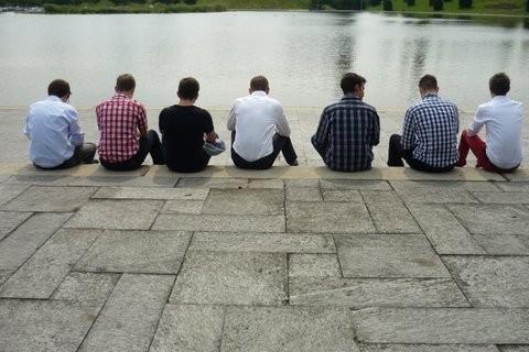 Das Foto zeigt junge Männer, die in einer Reihe an einem See sitzen, sie sind aber von hinten fotografiert.