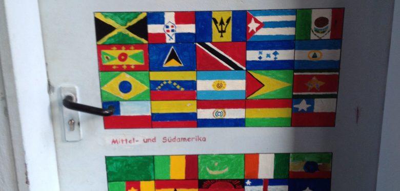 Das Bild zeigt eine Tür mit vielen Flaggen von Nationen rund um den Erdball.