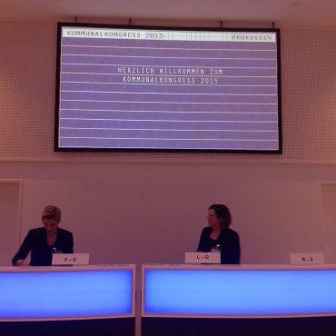 Das Foto zeigt den Anmeldeschalter vom Kommunalkongress in blauem Licht.