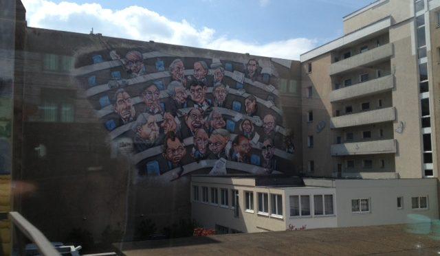Das Bild zeigt die Bemalung einer Häuserwand in Berlin, mit den Rängen des Dt. Bundestages.