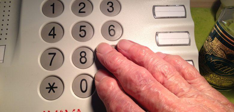Das Foto zeigt eine seniorengerechtes Telefon, im Vordergrund die Hand einer offensichtlich älteren Person.