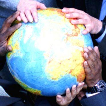 Verschiedene Mitarbeiter mit einem Globus in ihren Händen