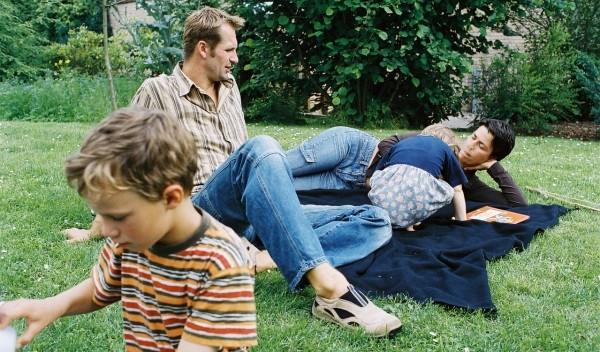 Familie die im Garten auf einer Wolldecke liegt