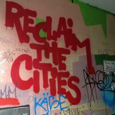 """Das Foto zeigt den Schriftzug """"Reclaim the Cities"""" als Grafiti an einer Häuserwand."""