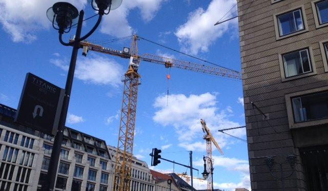 Das Foto zeigt viele Baukräne im Zentrum von Berlin vor einem blauen Himmel mit vielen Wolken.