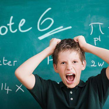 """Das Foto zeigt einen Schüler, der sich die Haare rauft vor einer Tafel mit einer """"sechs"""" drauf."""
