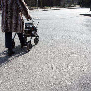 Das Foto zeigt eine Rollatorfahrerin auf der Straße.