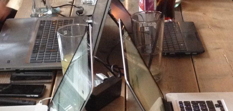 Das Foto zeigt viele aufgeklappte Notebooks auf einem Tisch.