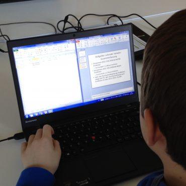 Das Foto zeigt einen jungen Mann, der über einem Rechner sitzt und hackt.