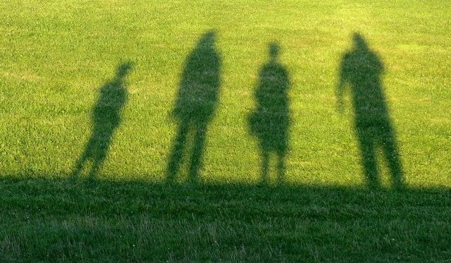 Das Foto zeigt eine Familie, die als Schatten auf grünen Rasen geworfen wird.