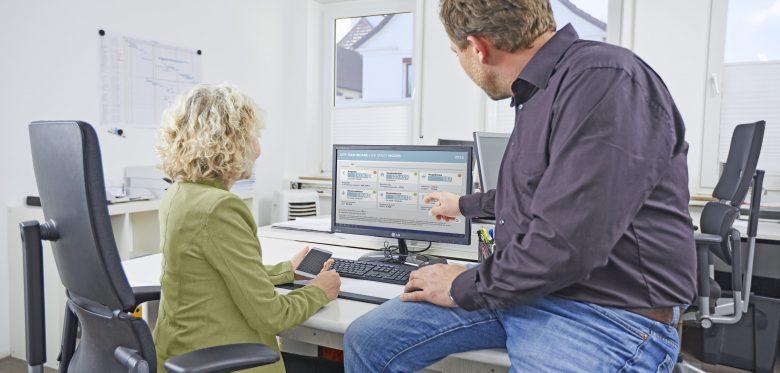 Eine Frau und ein Mann sitzen vor einem Monitor. Darauf zu sehen ist das Smart City Dashboard der Stadt Moers.
