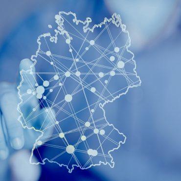 Eine Hand berührt ein Display auf dem eine Deutschlandkarte zu sehen ist mit vielen Punkten die untereinander verbunden sind