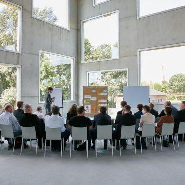 Zwei Dutzen Workshop-Teilnehmer sitzen in einem Halbkreis vor einer großen Glasfront. Vorne zu sehen ist ein Moderator mit einer Metplanwand und einer Flipchart