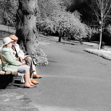 Ein älteres Ehepaar sitzt in einem Park auf einer Bank. Ihre Kleidung ist farbig, alles um sie herum schwarz und weiß