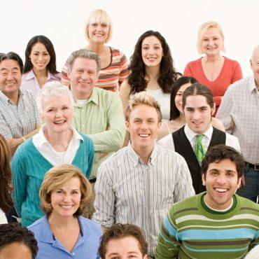 Eine Gruppe Menschen schaut in die Kamera: jung und alt, verschiedene Kulturen, Männer und Frauen. Alle lachen.