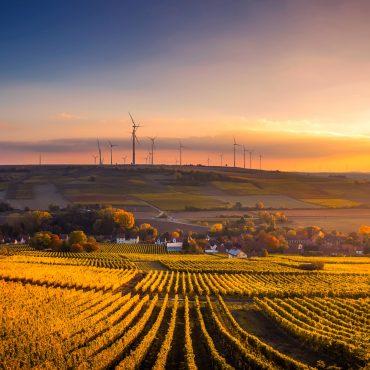 Blick auf eine hügelige Landschaft mit einem Dorf im Tal. Auf den Hügeln stehen windräder. Die Sonne geht unter