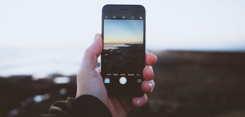 Eine Hand hält ein Smartphone auf das Meer. Zu sehen ist durch das Display das Meer und die Küste