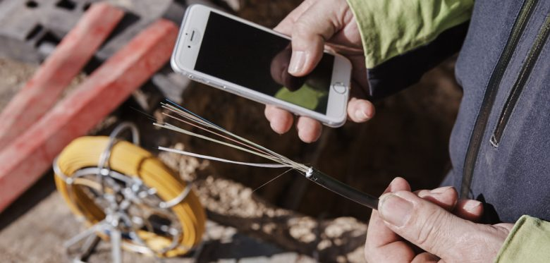 Zwei Hände eines Mannes. In der rechten Hand hält er ein Smartphone in de rlinken ein Glasfaserkabel.
