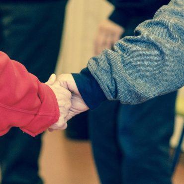 Die Hände zweier älterer Menschen die ineinandergreifen