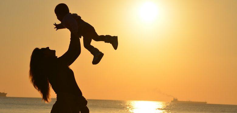 Eine Frau hält am Meer ein Baby in die Höhe. Die Sonne geht unter und die Frau und das Baby sind durch die glühende Sonne im Hintergrund nur in schwarz zu sehen.