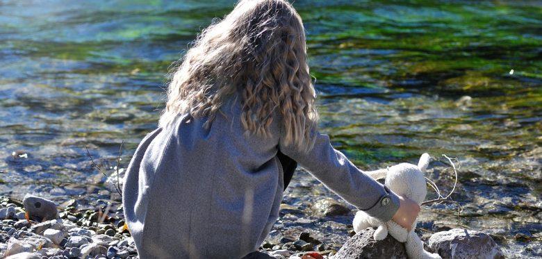Ein Kind hockt mit einem Kuscheltier am Ufer eines Flusses. Man sieht nur den Rücken des Mädchens.
