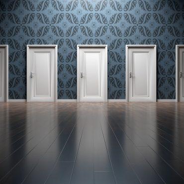 Mehrere geschlossene weiße Türen an einer einzigen Wand