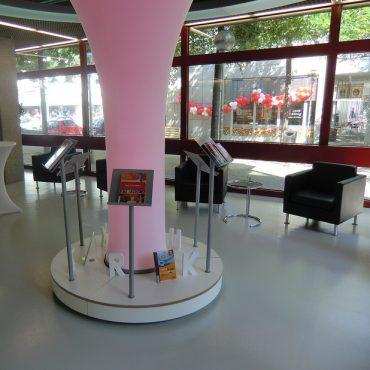 Leseraum in der Stadtbibliothek Köln. Einige Sessel und in der Mitte eine rosa leuchtende Säule mit Tablets auf Ständern drum herum