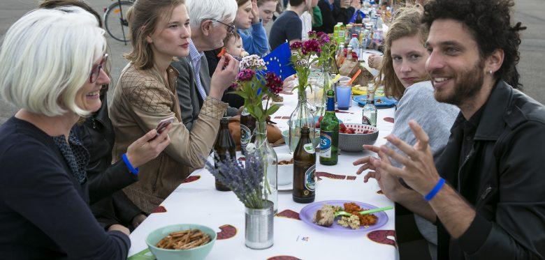 Blick auf einen langen Tisch, der draußen steht. An ihm sitzen viele Menschen unterschiedlicher Herkunft die sich unterhalten.