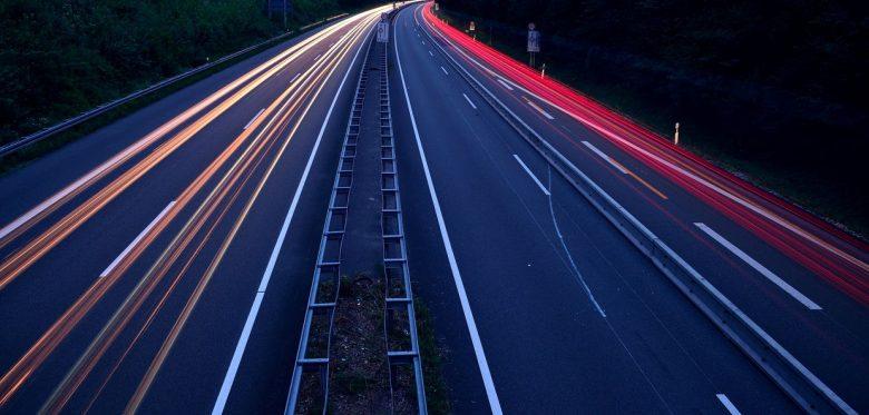 Autobahn bei Nacht. Man sieht keine Autos sondern nur Lichtstrahlen
