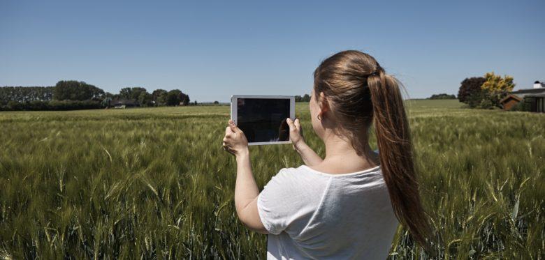 Eine Frau hält ein Tablet hoch. Im Hintergrund viele Wiesen und Bäume.