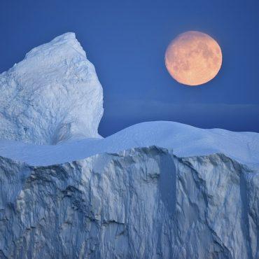 Blick auf einen Eisberg im Halbdunkel. Im Hintergrund scheint der Vollmond.