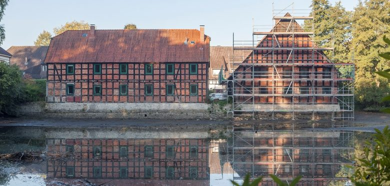 Von einem See Blick auf zwei alte Häsuer. Eines davon ist umgeben von Baugerüsten.