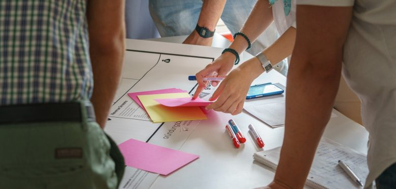 Viele Hände stützen sich auf einen Tisch. Auf dem Tisch liegt Papier und zahlreiche Post-its und Stifte