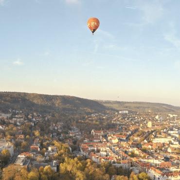 Blick auf Jena vom Jentower aus. Am Horizont ein Heißluftballon.