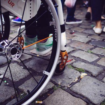 Blick auf die Räder eines Rollstuhls. Zu sehen sind auch noch die Füße auf der Fußablage des Rollstuhls.