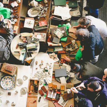 Blick aus Vogelperspektive auf einen Flohmarkt. Viele Tische um die herum ältere Menschen stehen.