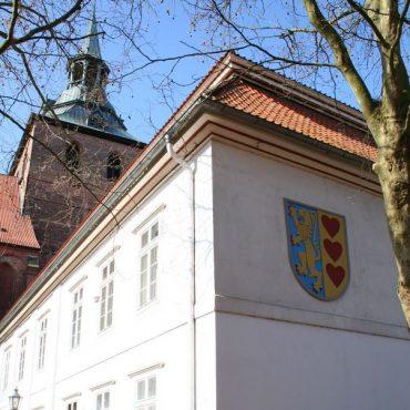 Das Gebäude der Landkreisverwaltung Lüneburg. Im Vordergrund ein weißes Gebäude mit dem Kreiswappen, im Hintergrund ein Kirchturm
