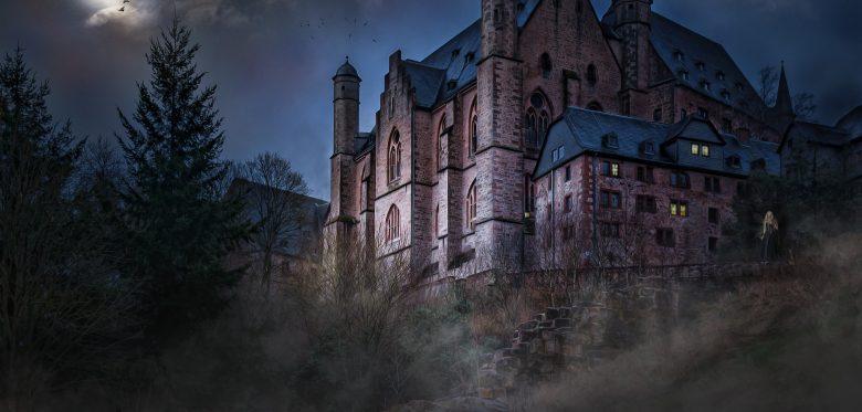 Blick auf eine Burg in der Nacht. Im Hintergrund strahlt der Vollmond.