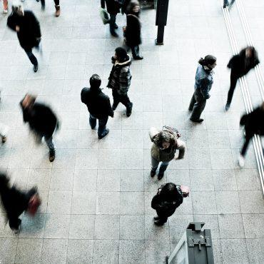 In einer Bahnhofshalle stehen einige Passanten und andere wiederum gehen an ihnen vorbei.