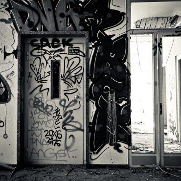 Schwarzweiß-Foto. Ein Aufzug in einem Treppenhaus, voll beschmiert mit Graffitti